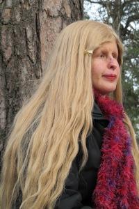 Sara Shamloo vid ett träd, har långt ljust hår och röd halsduk
