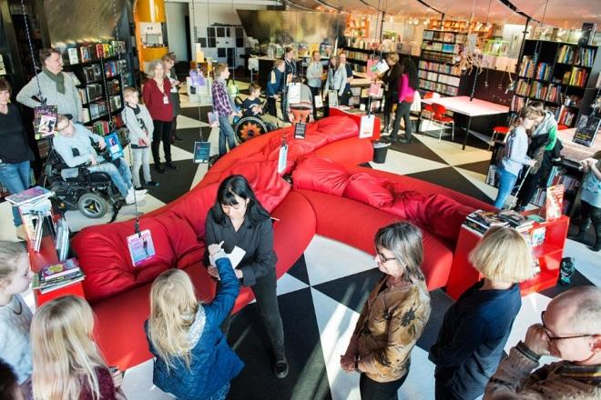 Barn och vuxna diskuterar bland röda möbler