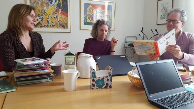 personer vid ett bord som tittar i barnböcker